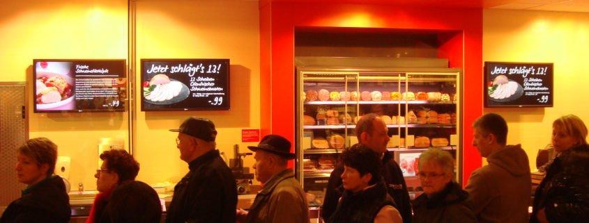 Digital Signage Diplay Angebot mit Personen an der Frischetheke