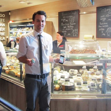 HIT Sütterlin Person an der Käsetheke zeigt iBeacon auf mobilem Endgerät