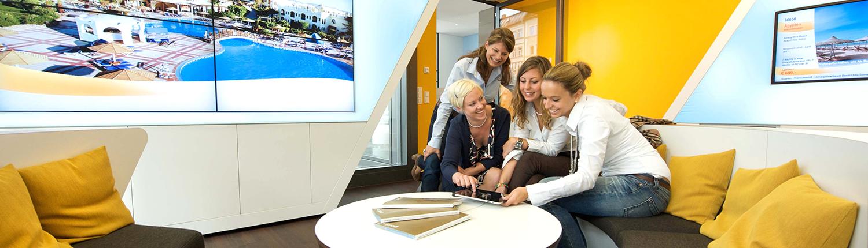 TVG Reisebüro Lounge mit Personen und Videowall Panorama