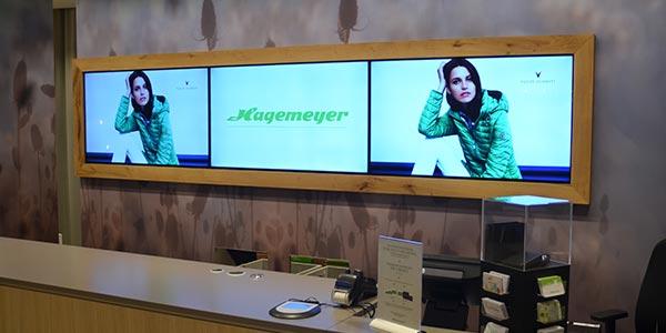 Bildschirme mit digitale Promotion hinter dem Kassentisch im Modehaus Hagemeyer