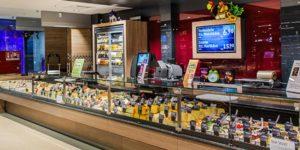 Bildschirme und Waagen mit Produktangeboten und Werbung an der Käsetheke im Supermarkt