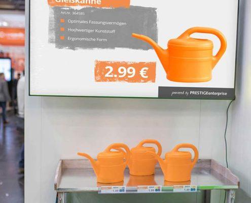 DIY Preisauszeichnung am Großformatbildschirm und Pflanzregal mit Kräutern und Gießkanne