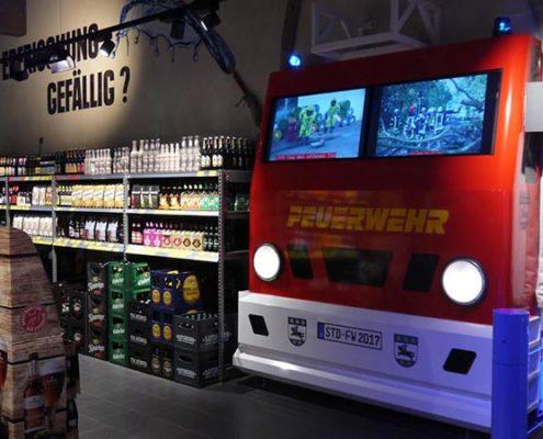 Feuerwehrattrappe mit Bildschirmen statt Frontscheibe im EDEKA Meibohm Getränkemarkt