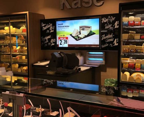Angebotswerbung für Käse auf einem Großformatbildschirm beim Einzelhändler EDEKA Meibohm