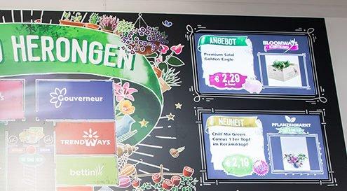 Digital Signage Bildschirme in einer großen Wand bei Landgard integriert zeigen aktuelle Angebote