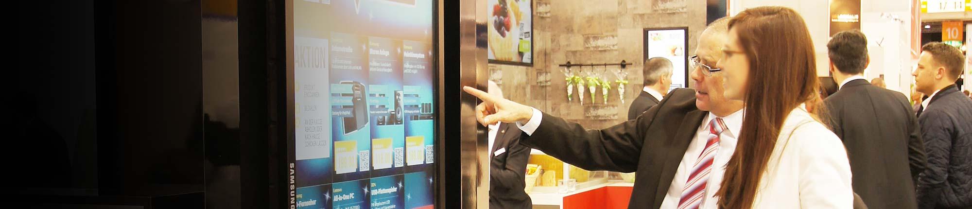 Kunden vor einem digitalen Regal bei der Produktinformation
