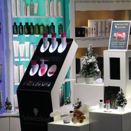 Eingangsbereich der Friseur Coiffina mit Haarpflege Produktdisplay inkl. sechs Bildschirmen