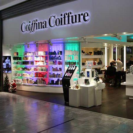 Filiale der Friseurkette Coiffina bewirbt Haarprodukte auf einem Produktdisplay mit 6 Bildschirmen