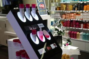 Produktdisplay mit 6 kleinen Bildschirmen bewerbt Haarprodukte bei der Friseurkette Coiffina