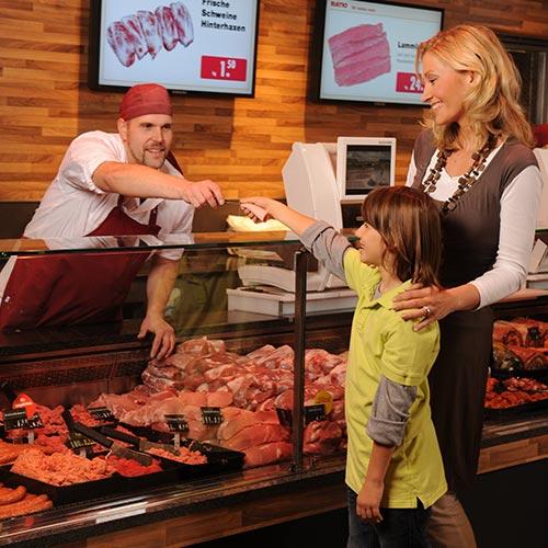 Fleischtheke mit Verkäufer und Mutter mit Kind