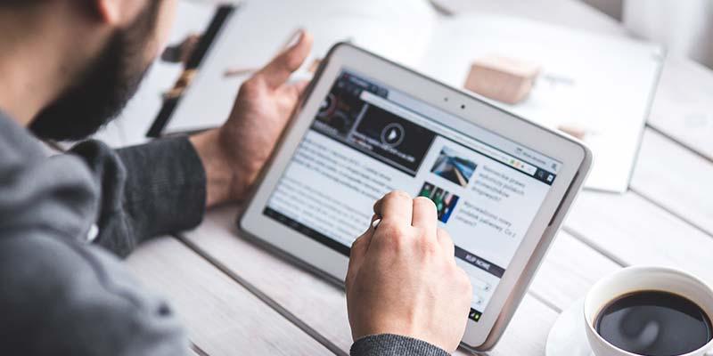 Online Software - Mann mit Tablet und Tasse Kaffee